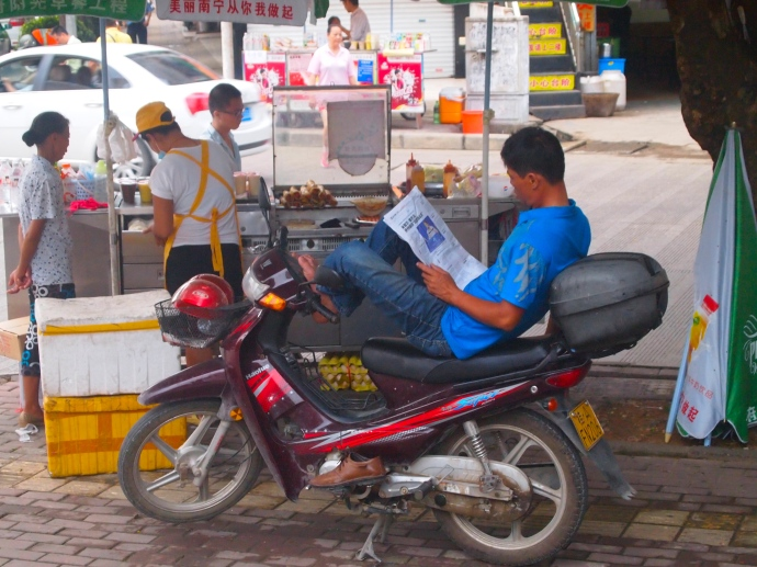 catching the morning news on a motorbike