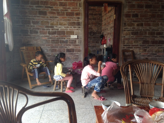 sitting with the children while the adults enjoy their cauldron of fish stew