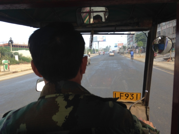 looking over the shoulder of the three-wheeled taxi driver