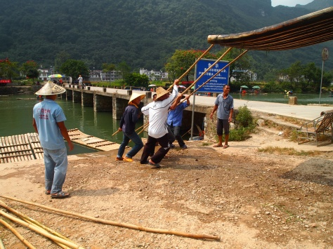 Men loading up the bamboo boats at Dragon Bridge