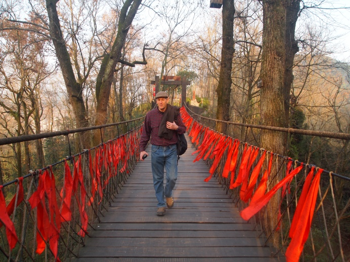 Mike walks across the swinging bridge