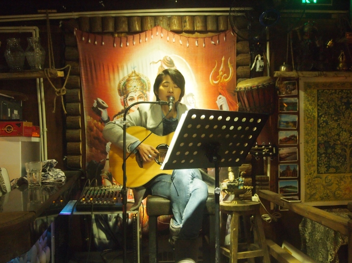 A Chinese girl sings folksy songs in a cafe