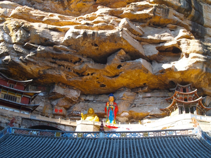 New statues of Guanyin and Maitreya, the smiling Buddha, on the cliff ledges at Baoxiang Temple