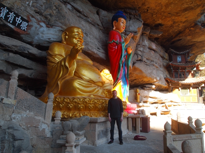 Alex stands beside Guanyin and Maitreya on the cliff ledges at Baoxiang Temple