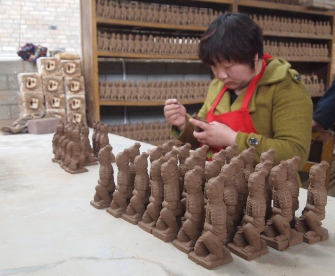 A woman carves terra cotta warriors