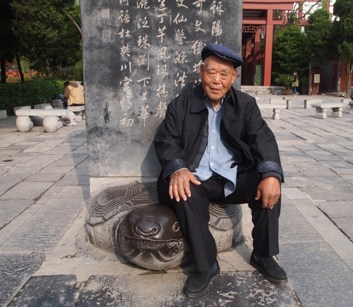 a kindly Chinese gentleman sits on a stele