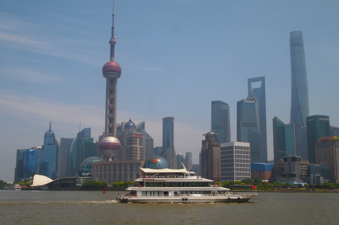 a ferry zips past Pudong