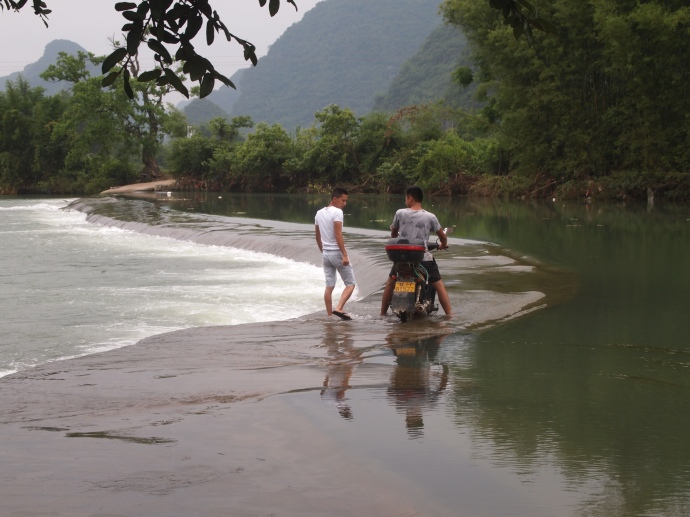 crossing the Yulong River on a motorbike