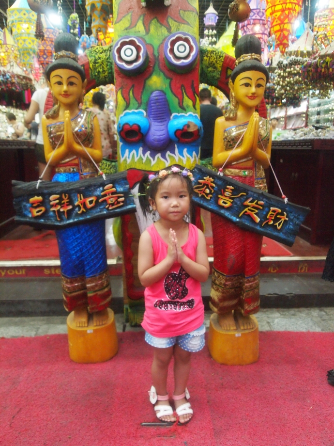 a little Chinese girl poses at a shop in Yangshuo