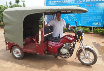 my driver and his red motor tricycle